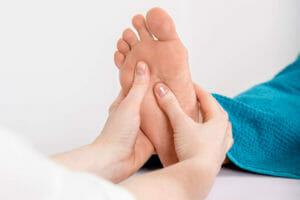 Massage der Fußreflexpunkte während der Fußreflexzonentherapie. Hier behandelt der rechte Daumen gerade die Nieren.