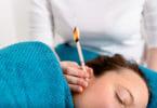 Das Flackern der Kerze massiert das Trommelfell während der Ohrenkerzenbehandlung.
